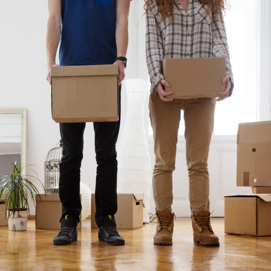 Couple holding moving boxes, relocating in Omaha, NE